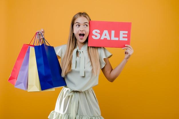 美しい興奮した若い女性は黄色で分離されたカラフルなショッピングバッグと販売サインを持っています