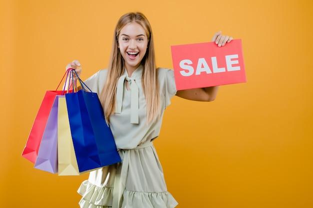 Счастливая усмехаясь милая молодая женщина с знаком продажи и красочные хозяйственные сумки изолированные над желтым цветом