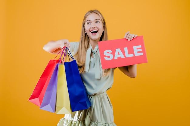 幸せな笑顔のかなり若い女性の販売サインと黄色で分離されたカラフルなショッピングバッグ