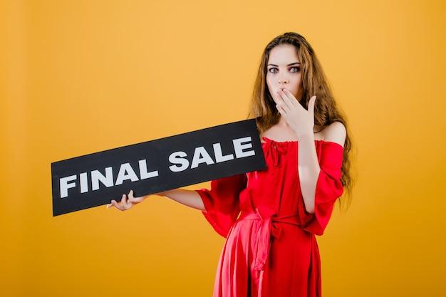 Удивлен молодая женщина имеет окончательный знак продажи, изолированных на желтом