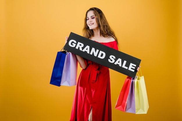グランドセールサインと黄色で分離されたカラフルなショッピングバッグを持つ魅力的な女性