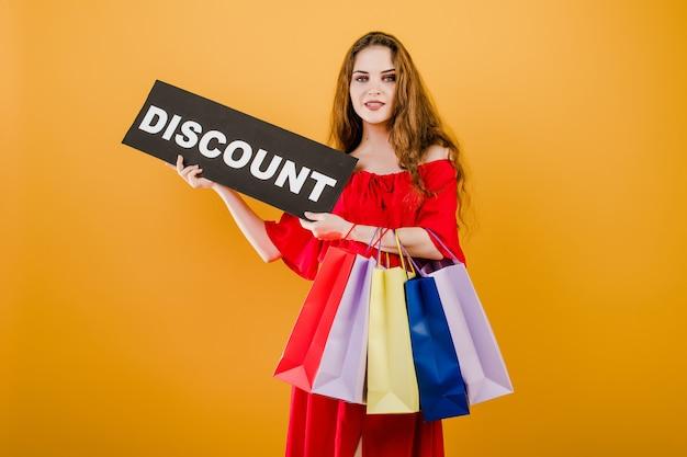 笑顔の若い女性は黄色で分離されたカラフルなショッピングバッグと割引記号を持っています