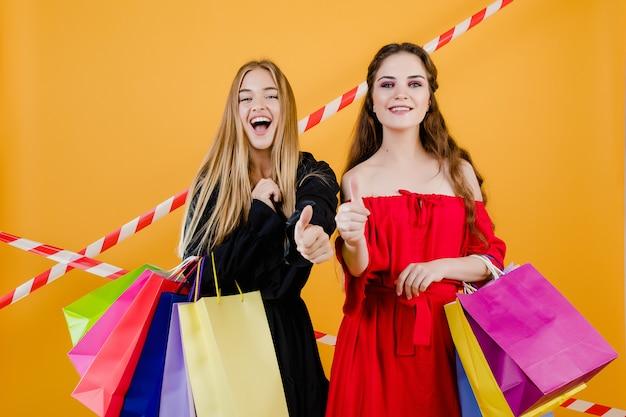 カラフルな買い物袋と黄色で分離された信号テープと美しい若い女性