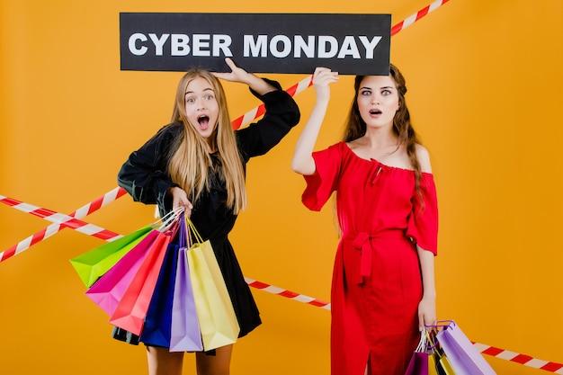 У двух удивленных красивых девушек есть знак кибер-понедельника с красочными сумками и сигнальной лентой, изолированных на желтом