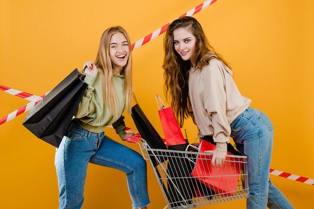 紙の買い物袋と買い物袋と黄色で分離された手押し車を持つ若いカジュアルな女性