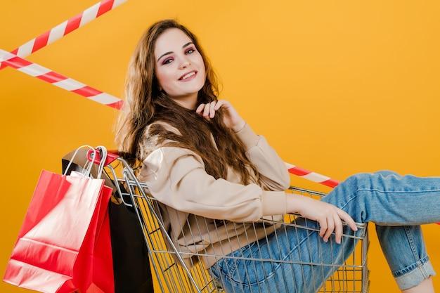 信号テープと黄色で分離された紙の買い物袋と手押し車の若い女性を笑顔