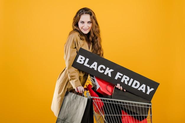黒い金曜日記号と黄色で分離された手押し車でカラフルなショッピングバッグと秋のトレンチコートの若い女性