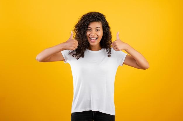 かなり黒人女性の笑みを浮かべて、黄色で分離された親指を表示