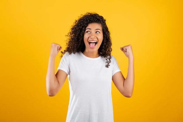 Счастливая африканская чернокожая женщина показывая ее победу изолированную над желтым цветом