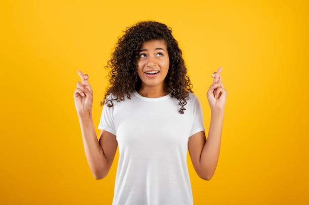 若い黒人女性を期待して、黄色で分離された交差指で祈る