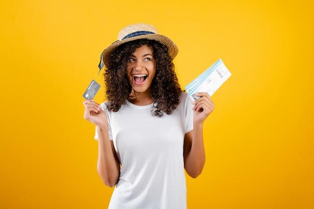 飛行機のチケットと黄色で分離された帽子をかぶっているクレジットカードと笑顔の幸せな黒人女性