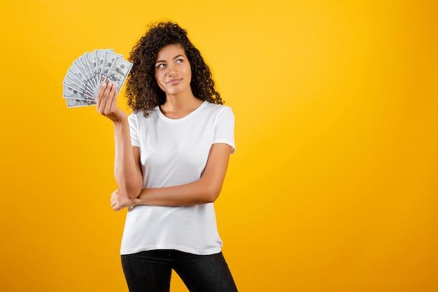 Молодая африканская чернокожая женщина с деньгами долларов в руке изолированная над желтым цветом