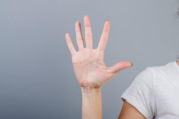 Женская рука в кулак, показывая пять пальцев, изолированных на серый