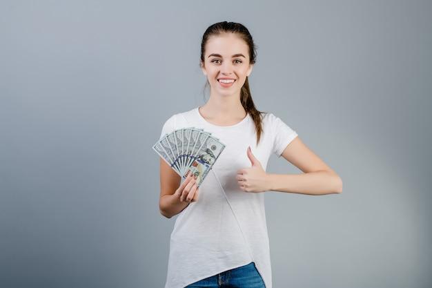 数百ドルを保持していると灰色で分離された親指を示す女性
