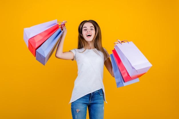 黄色で分離された空気中のジャンプカラフルな紙の買い物袋と幸せな笑顔の美しいブルネットの女性
