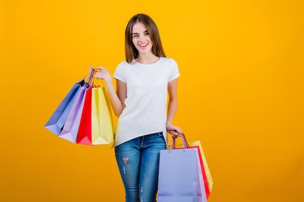 ジーンズとシャツは黄色で分離されたカラフルな紙の買い物袋と幸せな笑顔の美しいブルネットの女性