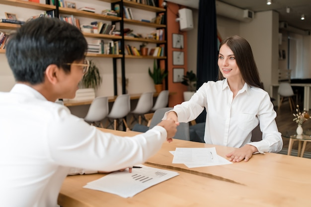 ビジネスマンのオフィスの会議場で若い実業家との契約に握手