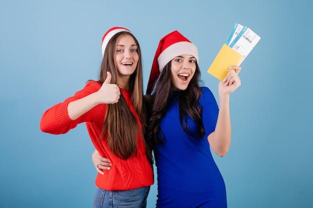 Две женщины в шляпах санта с билетами на самолет и паспортом, изолированных на синем