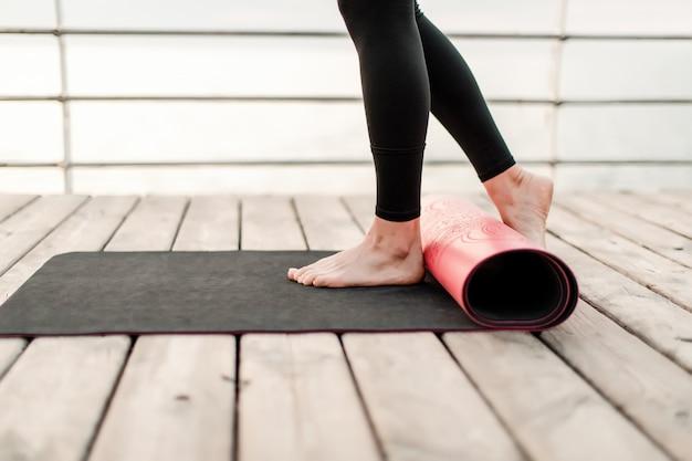 女性は日の出の海でアーサナトレーニングの前にヨガマットをロールします。