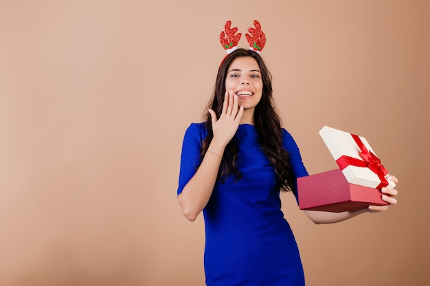 ギフト用の箱を保持していると茶色で分離された面白いクリスマスフープを着て笑顔美人
