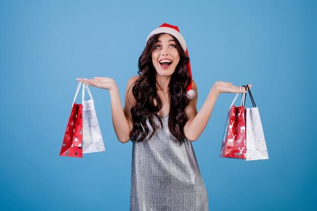 青で分離されたクリスマス帽子をかぶって買い物袋にプレゼントを持つ女性