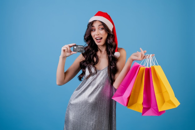 Женщина с красочными сумок и кредитной карты, носить шляпу рождество, изолированных на синий