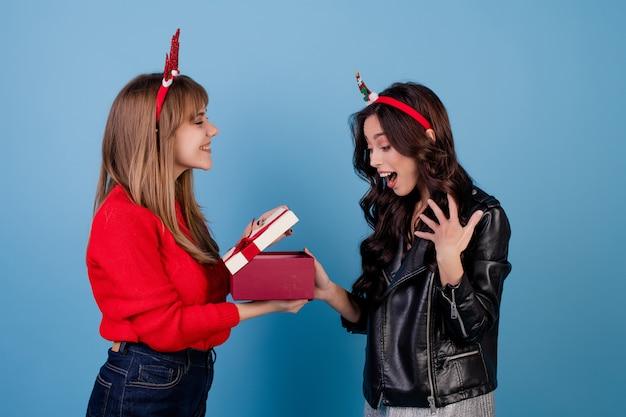青に分離された面白いクリスマスフープを着てリボン付きギフトボックスを持つ女性