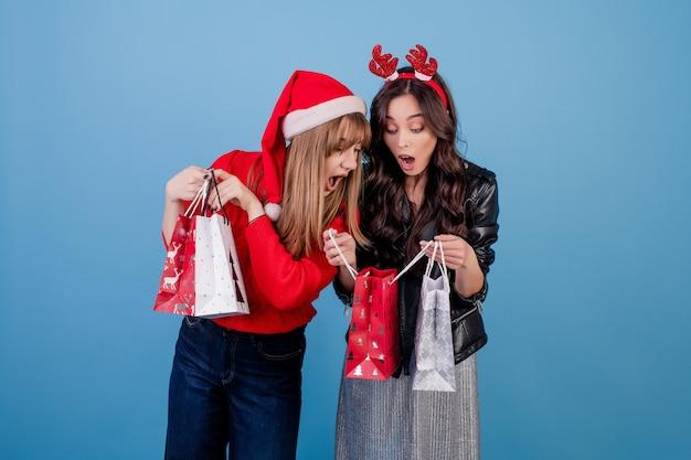 クリスマス帽子と青で分離された冬の服を着てカラフルなショッピングバッグにプレゼントを持つ女性
