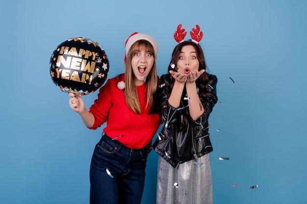 青で分離されたクリスマス帽子をかぶっている銀の紙吹雪を吹いて幸せな新年バルーンを持つ女性