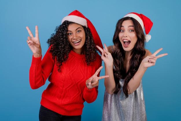 黒人女性と白人の女の子が青で分離されたクリスマス帽子をかぶって平和のジェスチャーを示す