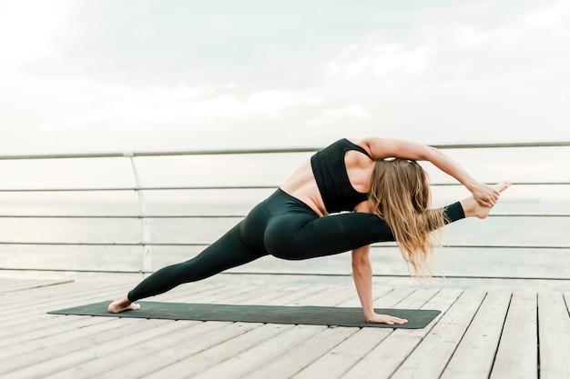 朝の日の出、海のそばのヨガのアーサナをやって、スポーツやフィットネスの練習を柔軟な女性