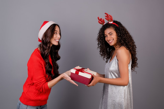 Разнообразные счастливых женщин с подарочной коробке с лентой, носить шляпу рождество, изолированных на серый