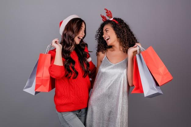 灰色で分離された赤いクリスマス帽子をかぶってカラフルな買い物袋を持つ多様な幸せな女性