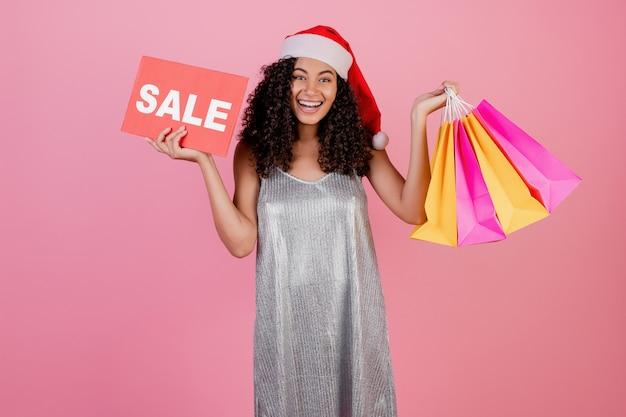 休日の買い物袋とピンクで分離されたクリスマス帽子をかぶって販売サインでプレゼントと美しい黒の女の子