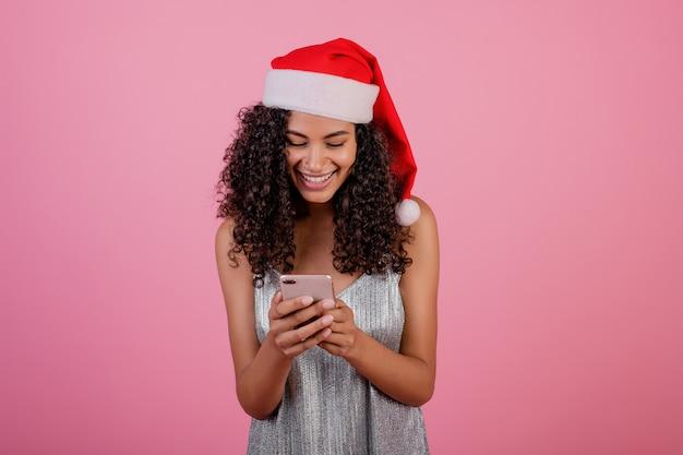 Красивая улыбающаяся темнокожая женщина с телефоном, носящая рождественскую шляпу и платье, изолированную по розовому цвету