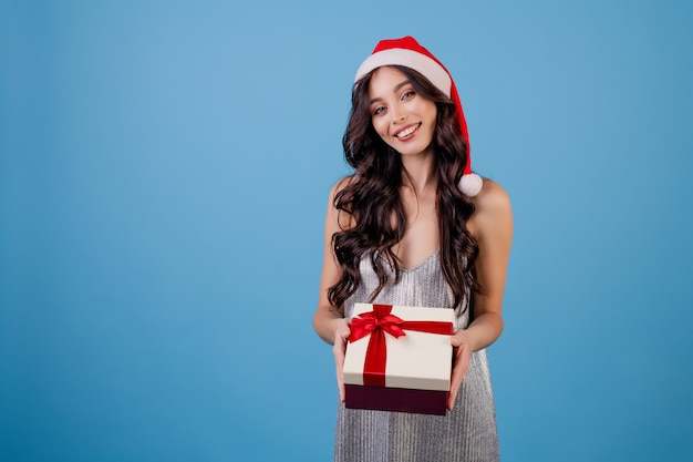 サンタの帽子をかぶっているギフトボックスを持つ女性