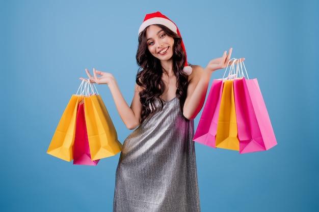 サンタの帽子とドレスを着てカラフルな買い物袋を持つ女性