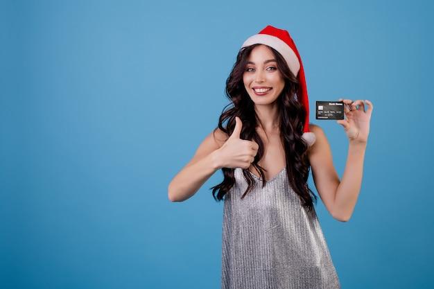 Женщина с кредитной картой в шляпе санта