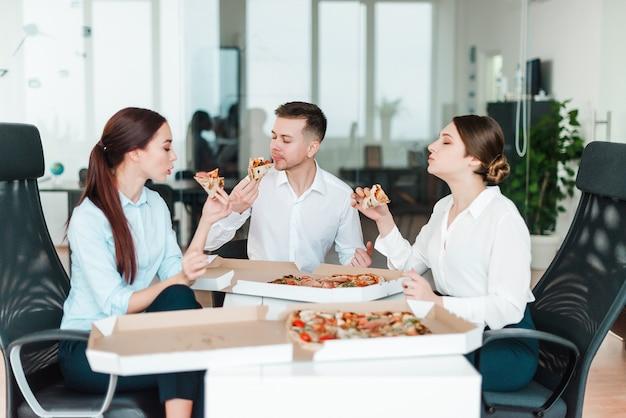 オフィスでピザの昼食を食べているビジネス人々