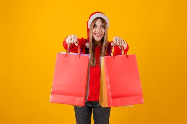 サンタの帽子とセーターを着てホリデーショッピングバッグの贈り物に興奮した女性