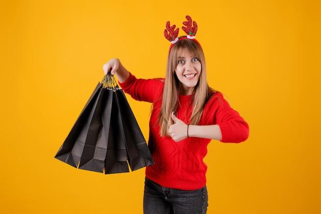 Взволнованная женщина с подарками в праздничных сумках в смешном обруче