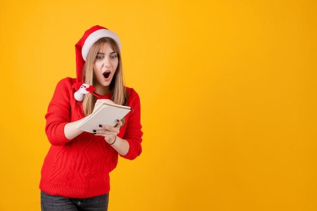 ノートとペンで新年の計画を書くノートを保持している女の子