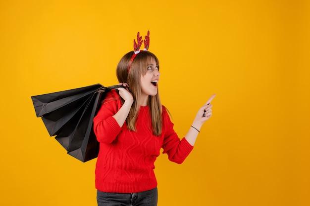 面白いフープを着てコピースペースを指してホリデーショッピングバッグに贈り物で幸せな女の子