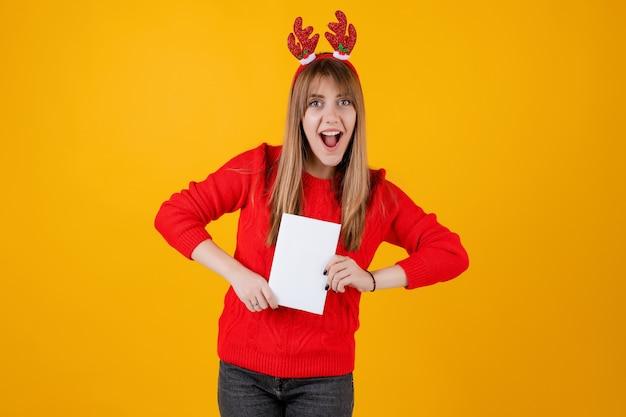コピースペースカバーが付いている本を保持し、面白いフープを着てスマート面白い女の子