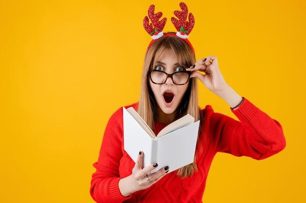 Умная смешная девушка держит книгу с копией пространства чтения с очками