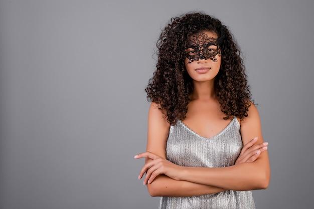 グレーで分離されたエレガントな仮面舞踏会マスクを身に着けている美しい黒人女性