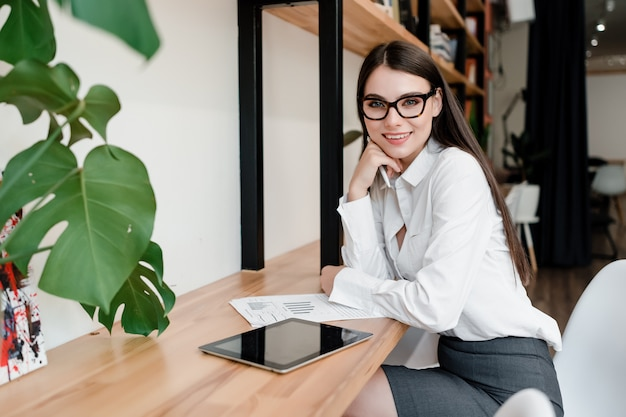 美しい実業家が机に座ってドキュメントとタブレットで動作します