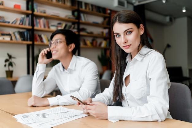 オフィスでアジアの同僚とドキュメントに取り組んでいる間電話を使用して美しいビジネス女性