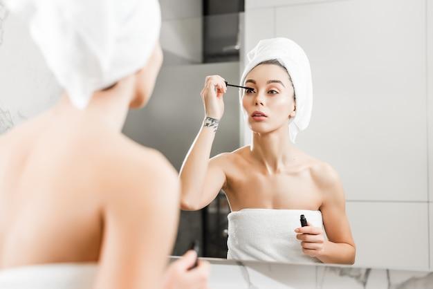 Красивая женщина, применяя тушь на ресницы, используя зеркало в ванной после душа
