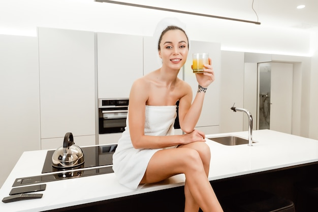タオルに包まれたシャワーの後の朝食にオレンジジュースを飲む美しい女性